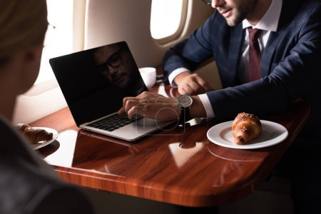 Photo for Cropped view of businesspeople working with laptop in airplane - Royalty Free Image