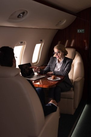 Photo for Professional business managers working with laptop in airplane - Royalty Free Image
