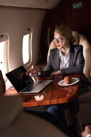 Foto de Mujer de negocios rubia trabajando en portátil en avión con croissant durante su viaje de negocios - Imagen libre de derechos