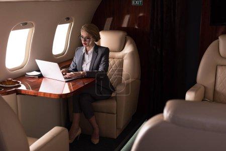 Photo pour Femme d'affaires confiante travaillant sur ordinateur portable dans l'avion pendant le voyage d'affaires - image libre de droit