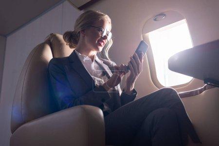 Photo pour Inquiet femme d'affaires parlant sur smartphone en avion pendant le voyage d'affaires - image libre de droit