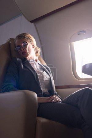 Photo pour Attrayant femme d'affaires dormir dans l'avion pendant le voyage d'affaires - image libre de droit