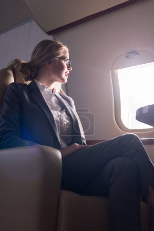 Photo pour Femme d'affaires en lunettes regardant la fenêtre dans l'avion pendant le voyage d'affaires - image libre de droit