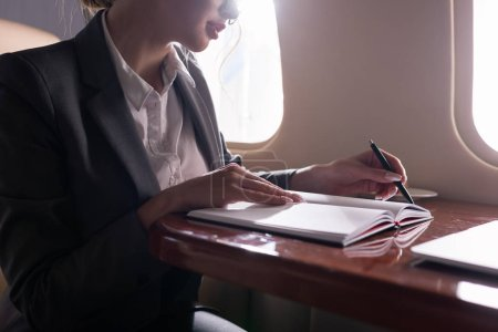 Photo for Cropped view of businesswoman working with documents in plane during business trip - Royalty Free Image
