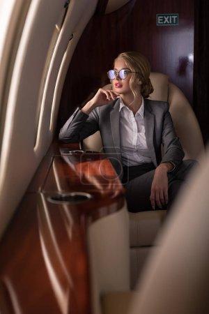 Foto de Beautiful businesswoman in glasses sitting in airplane during business trip - Imagen libre de derechos