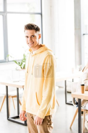 handsome young businessman in casual clothing smiling at camera