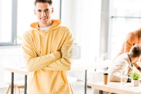 Photo pour Joyeux jeune homme d'affaires souriant à la caméra tout en se tenant avec les bras croisés dans le bureau - image libre de droit
