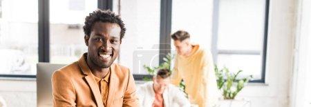 Photo pour Plan panoramique de jeune homme d'affaires afro-américain souriant à la caméra - image libre de droit