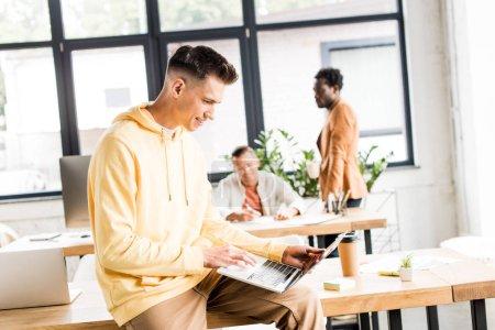 Photo pour Jeune homme d'affaires utilisant un ordinateur portable assis sur le bureau près de collègues multiculturels - image libre de droit