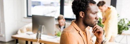 Photo pour Prise de vue panoramique d'un homme d'affaires afro-américain réfléchi regardant ailleurs alors qu'il était au bureau près de ses collègues - image libre de droit