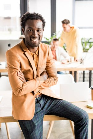 Photo for Smiling african american businessman sitting on desk with crossed arms - Royalty Free Image