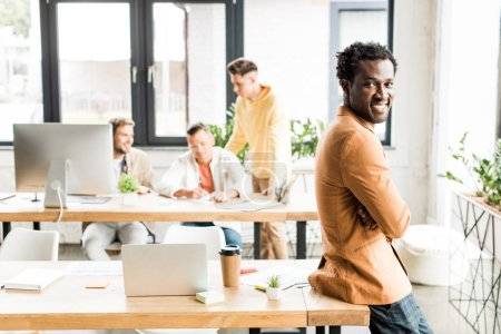 cheerful african american businessman looking at camera near colleagues working in office