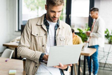 Photo pour Jeune homme d'affaires utilisant un ordinateur portable près de collègues travaillant dans le bureau - image libre de droit
