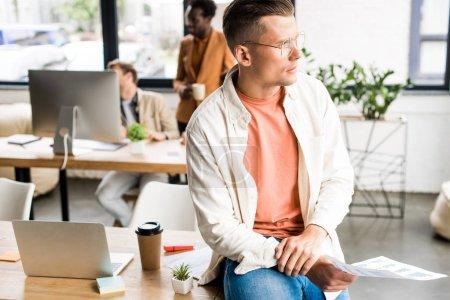 Photo pour Réfléchi, jeune homme d'affaires assis sur le bureau et regardant loin tandis que des collègues multiculturels travaillant dans le bureau - image libre de droit