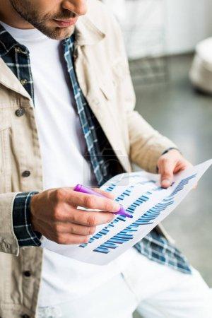 Photo pour Vue partielle d'un homme d'affaires tenant du papier avec des graphiques et des tableaux - image libre de droit