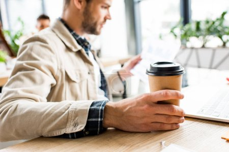 Photo for Selective focus of young businessman holding coffee to go while sitting at workplace in office - Royalty Free Image