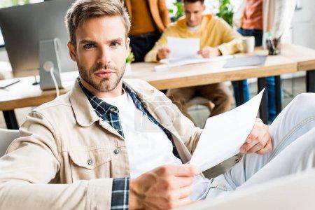 Photo pour Jeune homme d'affaires regardant la caméra tout en étant assis sur le lieu de travail au bureau - image libre de droit