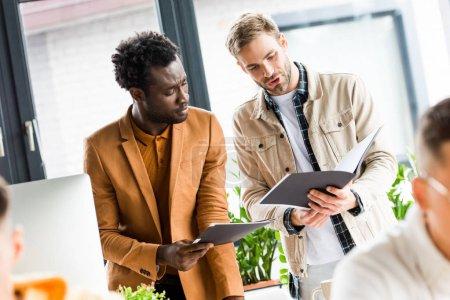 Photo pour Focalisation sélective de jeunes hommes d'affaires multiculturels cherchant dans des dossiers au bureau - image libre de droit