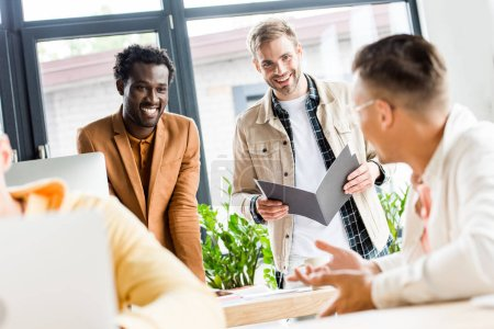 Photo for Selective focus of young multicultural businessmen talking and smiling in office - Royalty Free Image