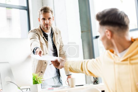 selective focus of young businessman giving paper to colleague in office