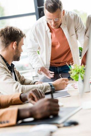 Photo pour Focalisation sélective des gens d'affaires multiculturels travaillant ensemble au bureau - image libre de droit