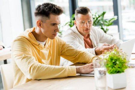 Photo pour Deux jeunes et beaux hommes d'affaires assis sur le lieu de travail et travaillant ensemble au bureau - image libre de droit