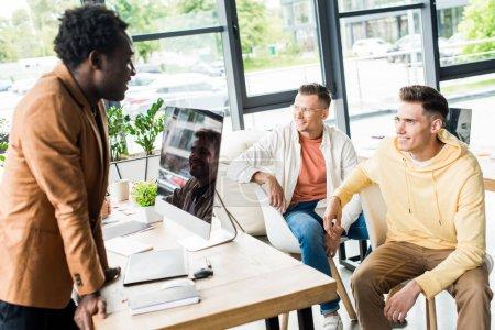 Photo pour De jeunes gens d'affaires multiculturels discutant d'un projet de démarrage au bureau près du lieu de travail avec un moniteur d'ordinateur - image libre de droit