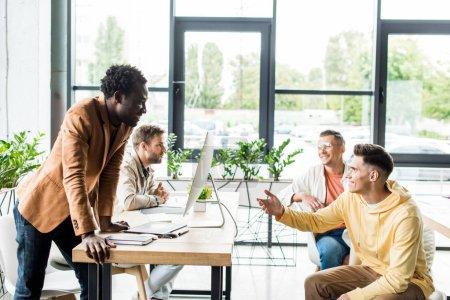 Photo pour Quatre hommes d'affaires multiculturels assis près du bureau et discutant ensemble d'un projet de démarrage - image libre de droit