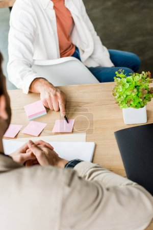 cropped view of businessman pointing at empty sticky note while sitting near colleague at workplace