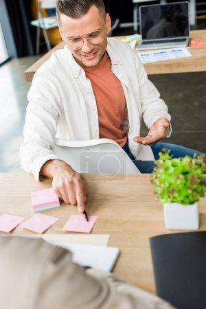 Photo pour Jeune homme d'affaires pointant vers vide note collante tout en étant assis près d'un collègue sur le lieu de travail - image libre de droit