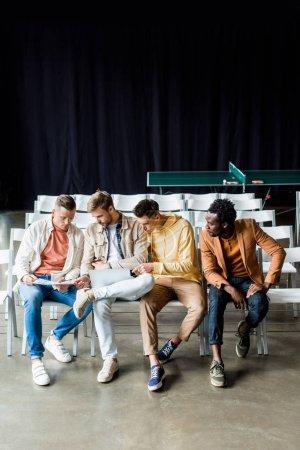 Photo pour Quatre jeunes hommes d'affaires multiculturels discutent d'un projet de démarrage dans une salle de conférence - image libre de droit