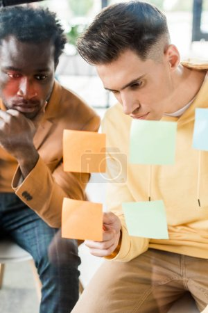 two multicultural businessmen looking at sticky notes fixed on glass board in office