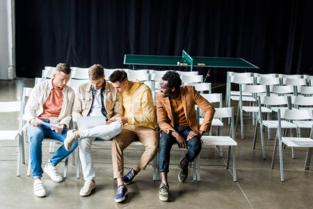 Photo for Four young multicultural businessmen discussing startup project while sitting in conference hall - Royalty Free Image