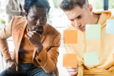 Photo pour Deux jeunes hommes d'affaires multiculturels regardant des notes collantes fixées sur un panneau de verre au bureau - image libre de droit