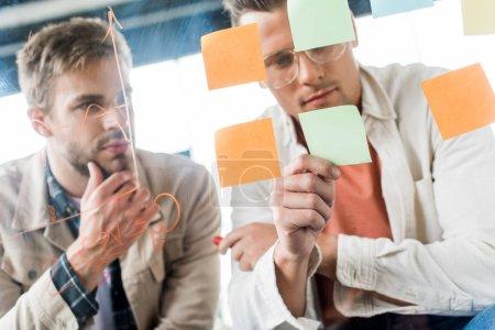 Photo pour Deux jeunes hommes d'affaires regardant des notes collantes fixées sur un panneau de verre au bureau - image libre de droit