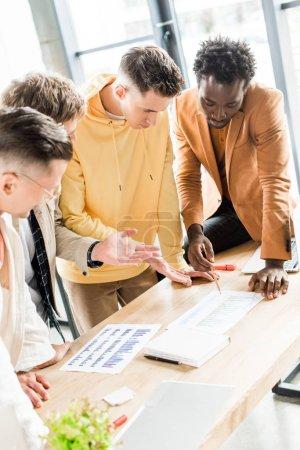 Photo pour Quatre hommes d'affaires multiculturels analysant des documents à l'aide de graphiques et de tableaux pendant qu'ils travaillent ensemble à un projet de démarrage au bureau - image libre de droit