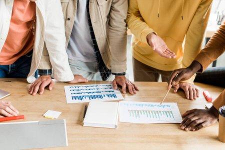 Photo pour Croisé vue de quatre gens d'affaires multiculturels analysant des documents avec des graphiques et des tableaux pendant qu'ils travaillent ensemble au projet de démarrage au bureau - image libre de droit