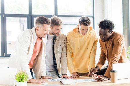 Photo pour Quatre jeunes gens d'affaires multiculturels analysant des documents à l'aide de graphiques et de tableaux pendant qu'ils travaillaient ensemble au bureau à un projet de démarrage - image libre de droit