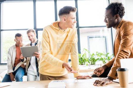 Photo pour De jeunes hommes d'affaires muticulturels discutant alors que leurs collègues regardent une chemise dans leur bureau - image libre de droit