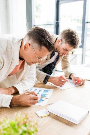 Photo pour Deux jeunes hommes d'affaires analysent des documents à l'aide de graphiques et de tableaux pendant qu'ils travaillent ensemble à un projet de démarrage au bureau - image libre de droit