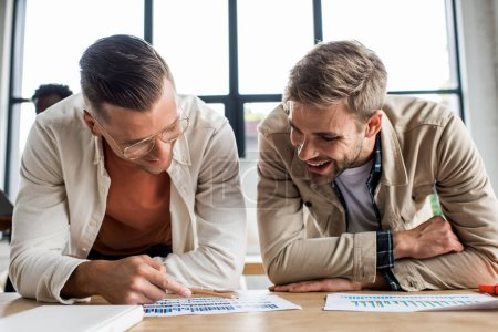 Photo for Two young smiling businessmen analyzing papers with graphs and charts while working on startup project together in office - Royalty Free Image