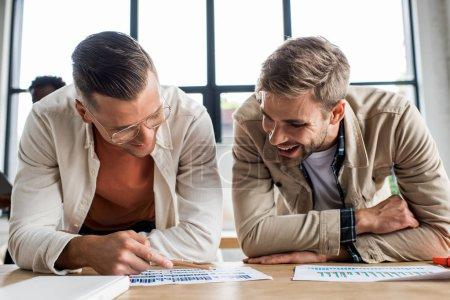 Photo pour Deux jeunes hommes d'affaires souriants analysant des documents à l'aide de graphiques et de tableaux pendant qu'ils travaillaient ensemble à un projet de démarrage au bureau - image libre de droit