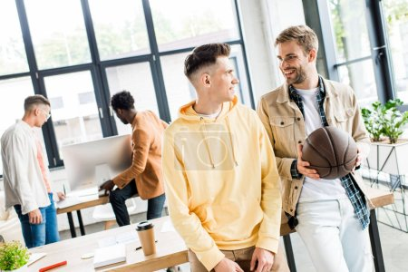 smiling businessman holding volleyball while talking to colleague in office