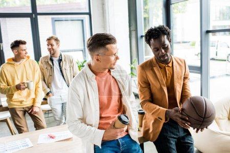 Afrikanisch-amerikanischer Geschäftsmann mit Volleyball im Gespräch mit einem Kollegen, der Coffee to go im Büro hält