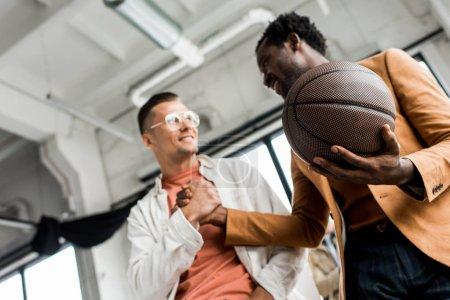 Photo pour Vue à angle droit d'un homme d'affaires américain d'origine africaine tenant du volley-ball et serrant la main d'un collègue en fonction - image libre de droit