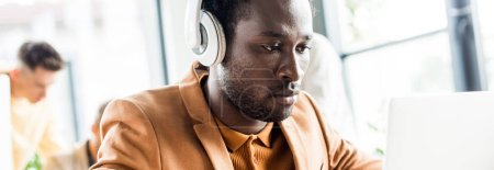 panoramic shot of handsome african american businessman in headphones working in office