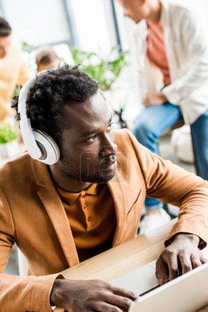 Photo pour Grave homme d'affaires afro-américain dans les écouteurs à l'aide d'un ordinateur portable au bureau - image libre de droit