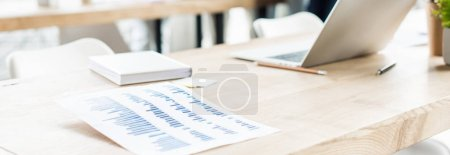 Photo for Panoramic shot of desk with laptop, notebook and paper with graphs and charts in office - Royalty Free Image