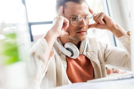Photo pour Foyer sélectif d'homme d'affaires coûteux assis sur le lieu de travail avec écouteurs sur le cou - image libre de droit