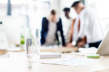 Photo pour Focalisation sélective du verre avec de l'eau sur le bureau près des gens d'affaires debout sur les lieux de travail - image libre de droit